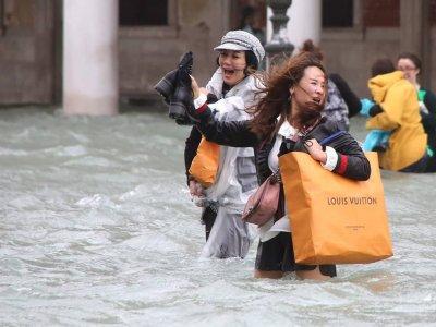 Frauen mit Einkaufstüten während des alljährlichen Hochwassers in Venedig. Foto: Claudia Manzo