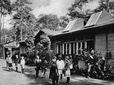 1904 entstand die erste Waldschule in Charlottenburg, nahe Berlin, in den Ausläufern des Grunewalds. Sie wurde für kränkliche Kinder errichtet, die in den Städten dem Risiko der Tuberkuloseerkrankung ausgesetzt waren. Foto: Waldschule Charlottenburg, via Wikimedia Commons, gemeinfrei.