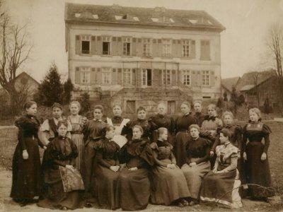 Der erste Jahrgang 1897–1898 einer Reifensteiner Schule in Nieder-Ofleiden. Abgebildet mit Freifrau von Schenck zu Schweinsberg, einer wichtigen Förderin der Schulen. Bild: Reifensteiner Verband (CC BY-SA 3.0).